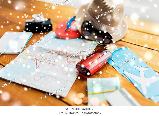 tourism, winter holidays and objects concept - close up of travel map, airplane tickets, money and personal accessories