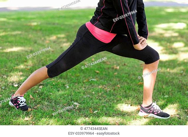 Low section of a healthy young woman doing stretching exercise in the park