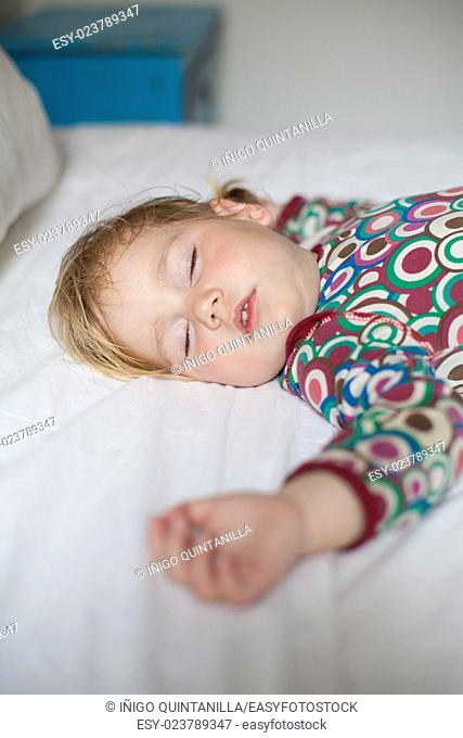 blonde caucasian baby face nineteen month age with colored shirt sleeping on white sheets king bed