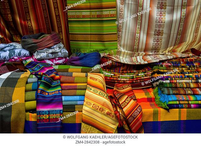 Colorful fabrics for sale on the crafts market in the town of Otavalo in the highlands of Ecuador near Quito