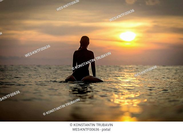 Indonesia, Bali, female surfer in the ocean at sunset