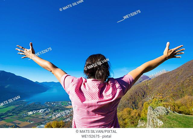 Rear View of Woman with Arms Outstretched on Mountain with Alpine Lake Maggiore in Ticino, Switzerland