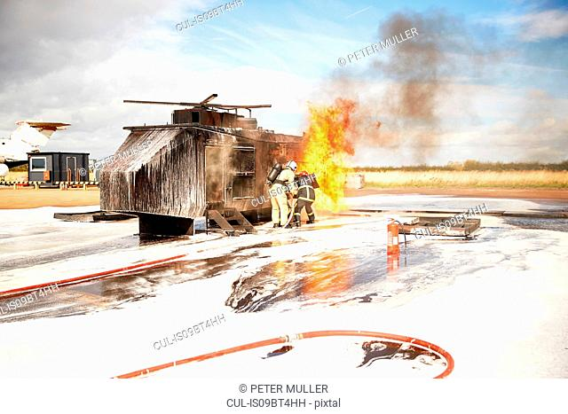 Firemen training, team of firemen spraying firefighting foam at mock helicopter fire at training facility