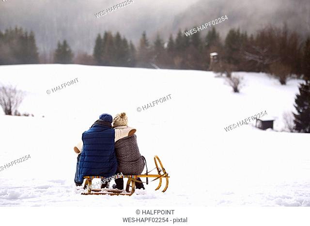 Back view of senior couple sitting side by side on sledge in snow-covered landscape