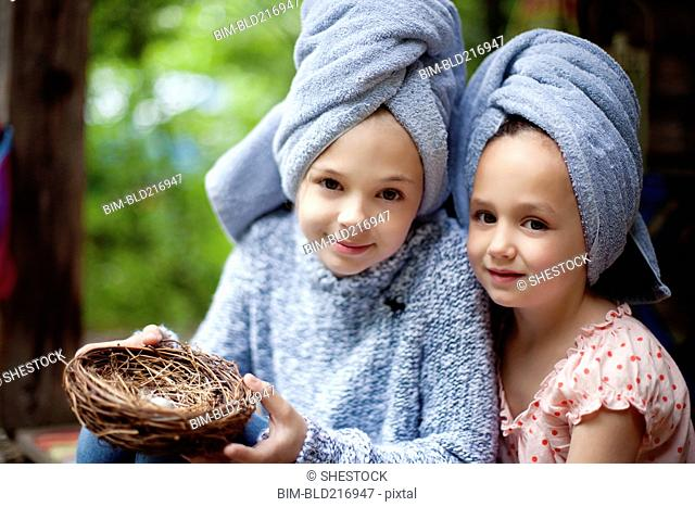 Caucasian sisters in hair towels holding bird nest