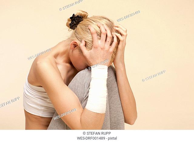 Despaired young woman sitting with head in hands and bandage around arm