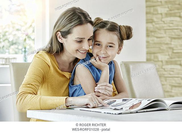 Happy mother with daughter at home looking at picture book