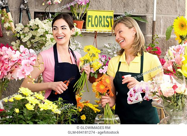 Two female florists working in a flower shop and smiling