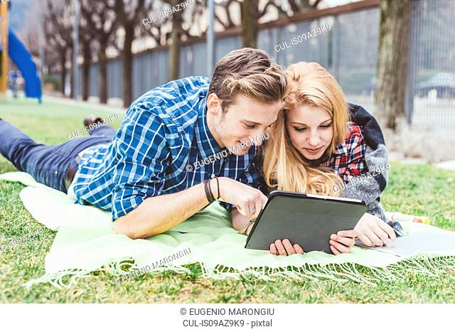 Young couple lying on picnic blanket looking at digital tablet, Lake Como, Italy