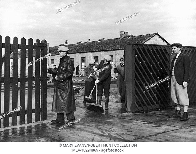 The concrete road by the main gate of Kitchener camp is kept clean. The refugee on the left, whose wife and daughter have emigrated to the Bronx