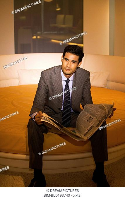 Businessman reading newspaper on round bed