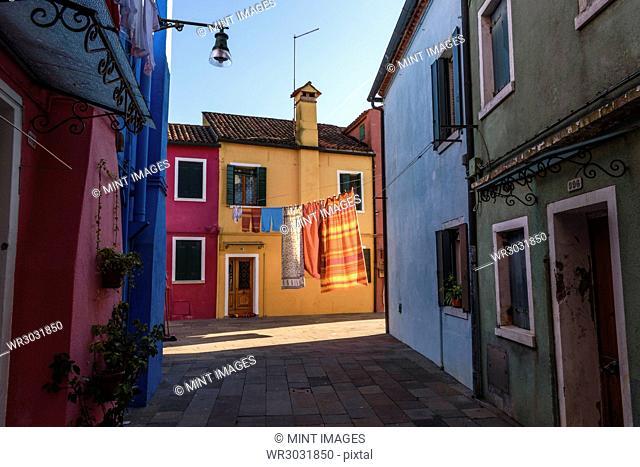 Narrow alley with colourful facades and clothes on washing line in Venice, Italy