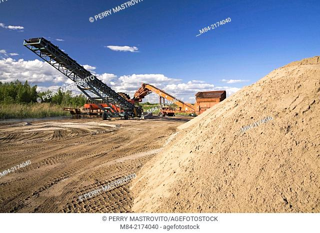 Stacking conveyor and a screener next to a mound of sand in a commercial sandpit, Quebec, Canada