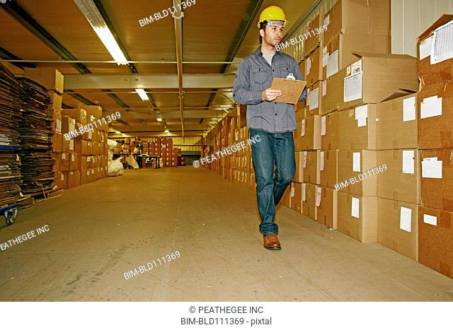 Caucasian worker checking product in warehouse