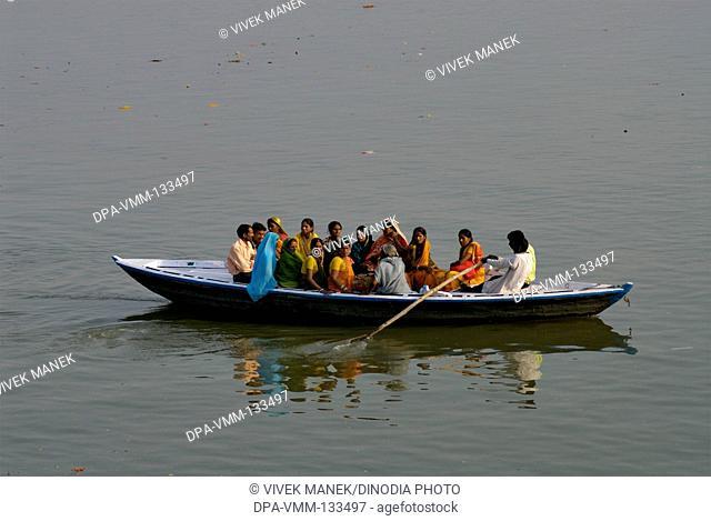 Indian men and women enjoying boat ride in Ganga holy River ; Varanasi ; Uttar Pradesh ; India