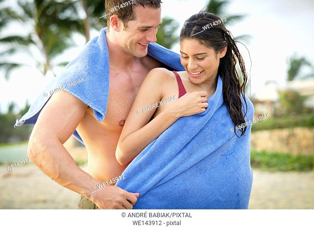 Young man drying his woman with towel at a beach