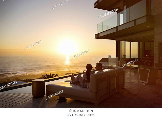 Tranquil sunset ocean view beyond silhouette of couple on luxury home showcase chaise lounge