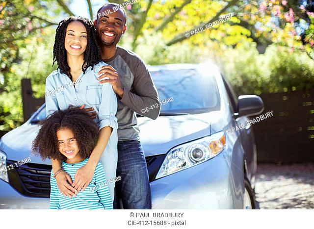 Portrait of happy family outside car