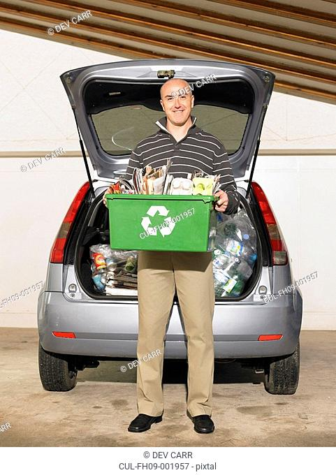 Man standing in front of car holding box of recycling, smiling, portrait