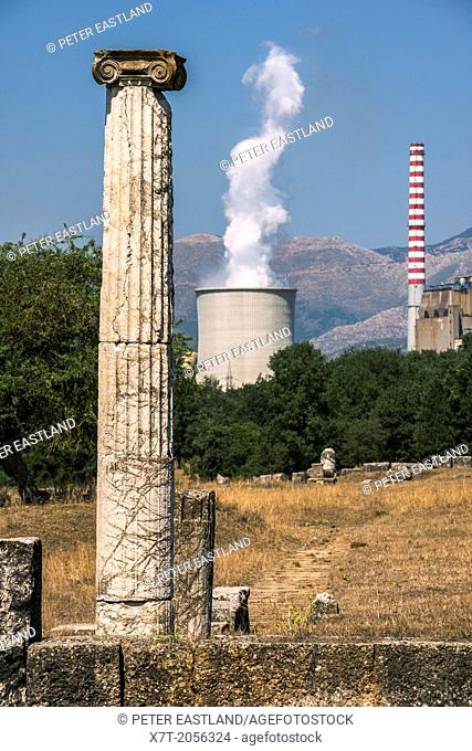 An ionic column from the ruins of Ancient Megalopolis with the cooling tower and chimney of Mergalopolis modern power station in the background
