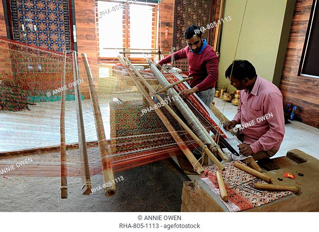 Two men working together to weave a complex double ikat Patola sari using a harness loom slanted to one side, Patan, Gujarat, India, Asia