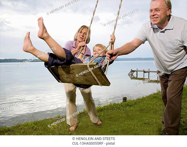 grandparents with grandson on swing