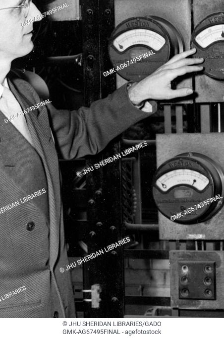 American television host Lynn Poole on set of the Johns Hopkins Science review television program looking at an analog gauge, 1951