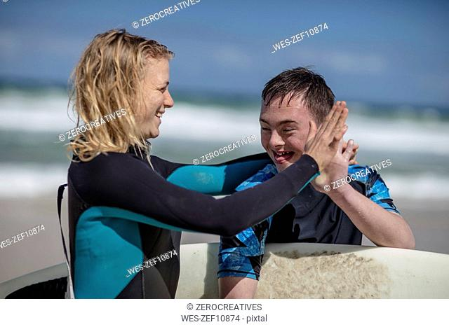 Happy teenage boy with down syndrome and woman with surfboard on beach