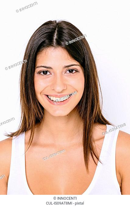 Portrait of young woman wearing white vest looking at camera smiling