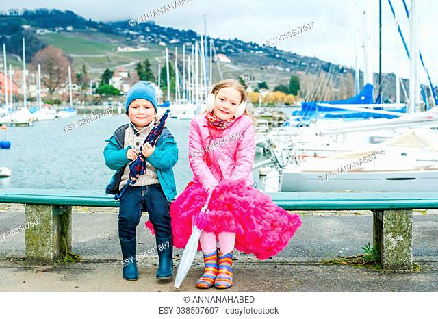 Cutr children sitting on a bench on a cold spring day