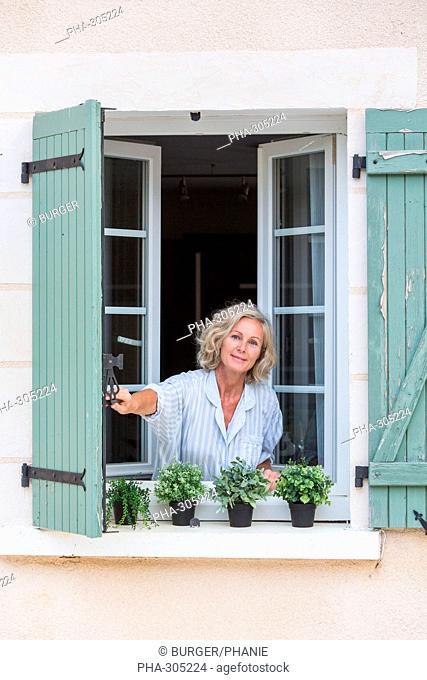 Woman opening shutters