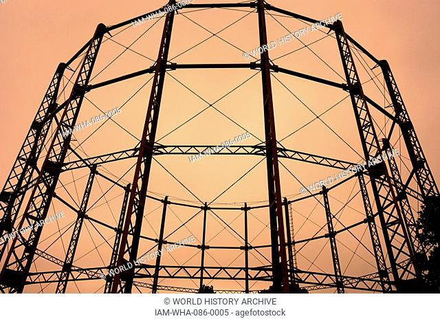 A gas holder. A large container in which natural gas or town gas is stored near atmospheric pressure at ambient temperatures. London