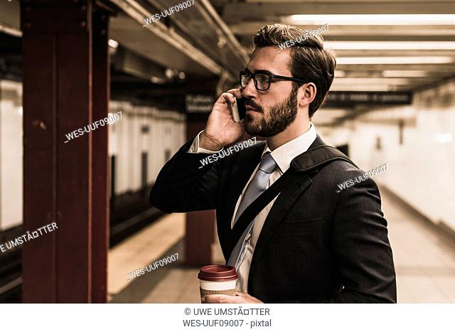 Young businessman waiting at metro station platform, using smart phone