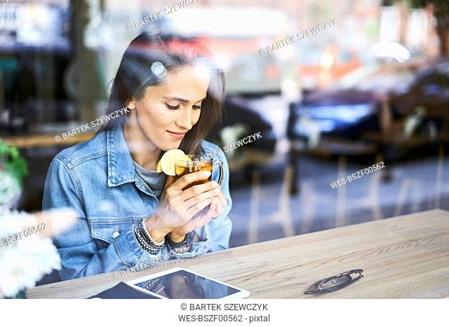 Smiling young woman having tea in cafe