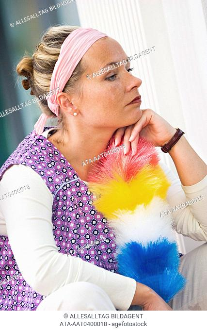 Thoughtful woman with duster