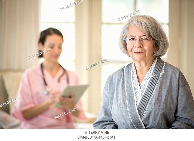 Smiling older woman in bathrobe with nurse