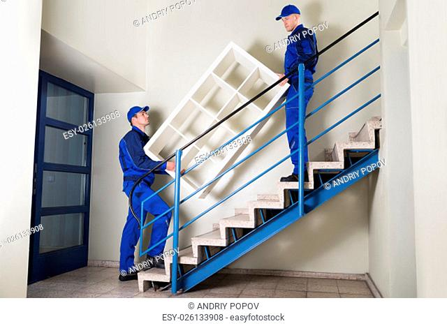Full length of young movers carrying shelf while climbing steps at home
