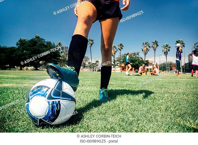 Waist down of teenage schoolgirl soccer player with foot on ball on school sports field