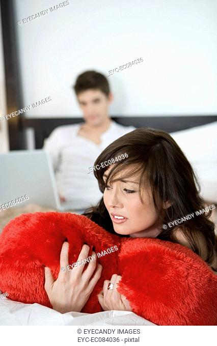 Portrait of sad young woman hugging red heart pillow in bedroom with man on laptop behind