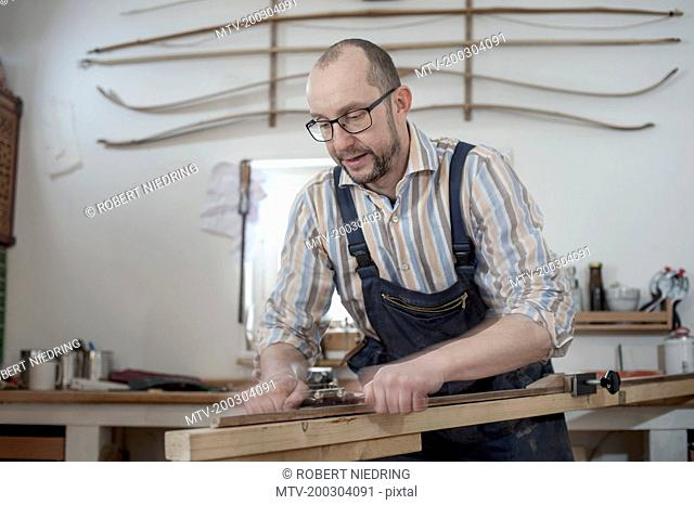Male bow maker shaving wood and giving it a shape of bow in workshop, Bavaria, Germany