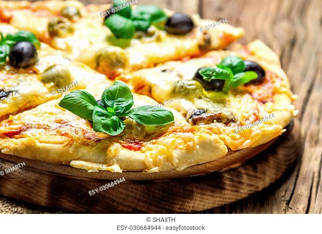 Closeup of freshly baked pizza with cheese and basil