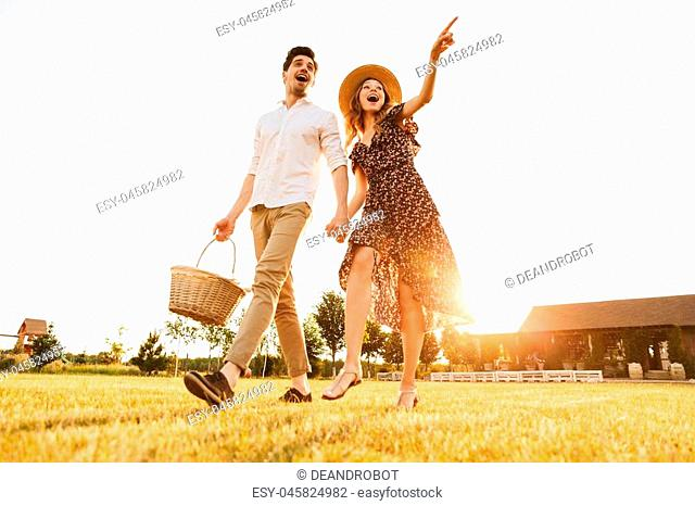Happy young couple with basket of drinks and food going to have picnic outdoors pointing