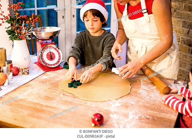 Mother and son making Christmas cookies at home