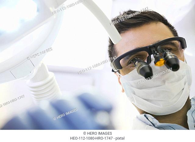 Dentist in dental loupes performing checkup