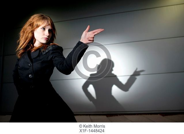 A late teen early 20s single woman girl with red hair pointing her fingers like a gun, casting shadow, UK
