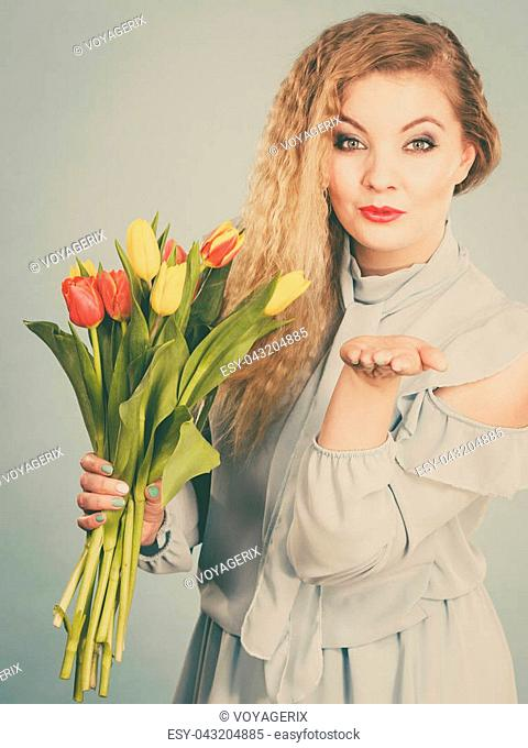 International women day, eight march. Beautiful portrait of pretty woman blonde hair with red yellow tulips, fashion make up. Mother day. Toned image