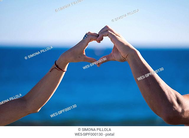 Spain, Tenerife, hands of couple building a heart