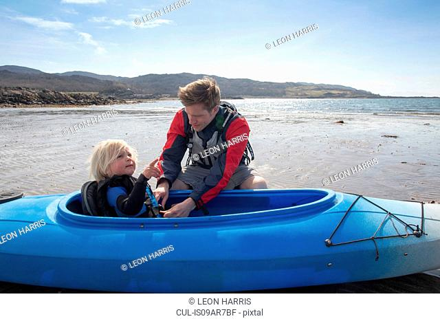 Father helping son in canoe, Loch Eishort, Isle of Skye, Hebrides, Scotland
