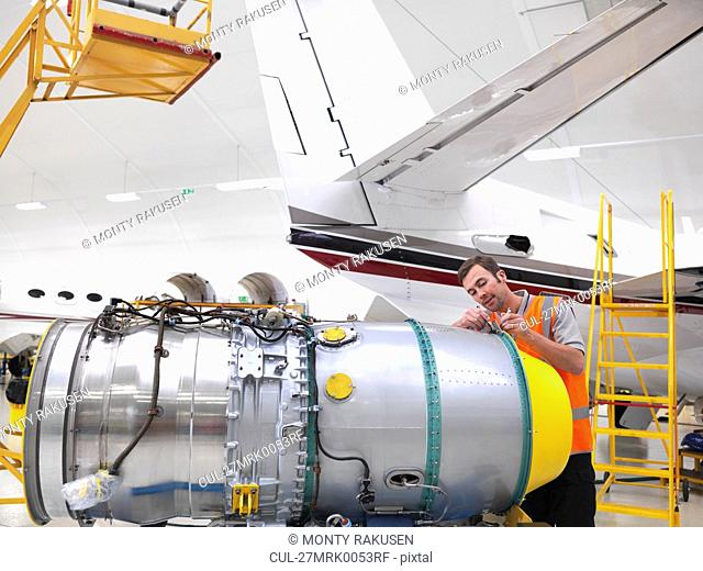 Engineer working on jet aircraft engine