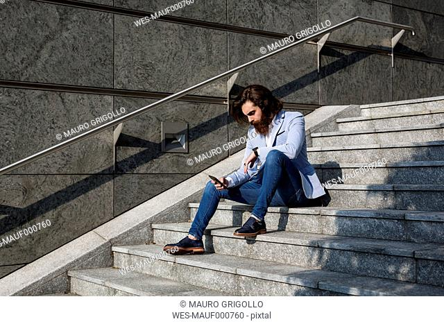 Stylish businessman using cell phone on stairs outdoors